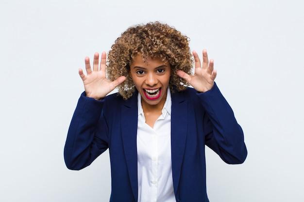 Młoda kobieta, afroamerykanin krzyczy w panice lub gniewu, zszokowany, przerażony lub wściekły, z rękami obok głowy