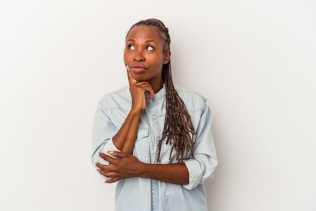 Młoda kobieta afroamerykanin na białym tle kontemplując, planując strategię, myśląc o sposobie prowadzenia biznesu.