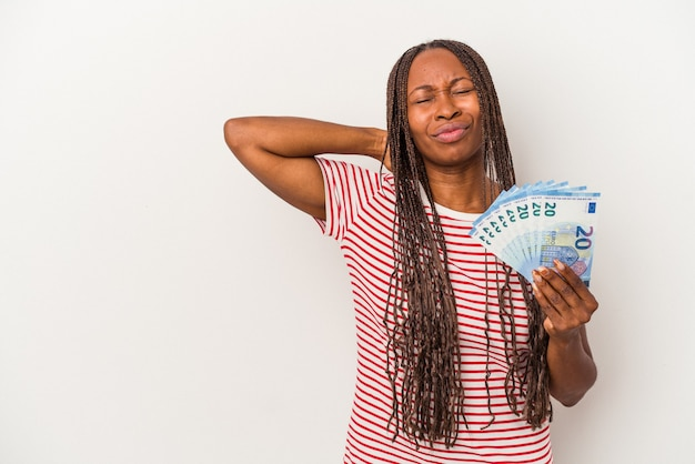 Młoda kobieta afroamerykanin trzyma banknoty na białym tle dotykając tyłu głowy, myśląc i dokonując wyboru.