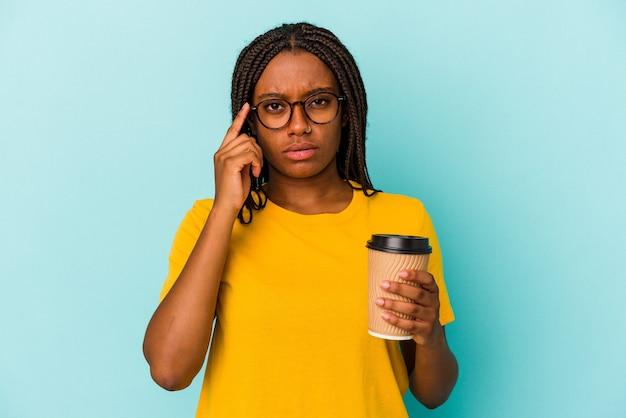Młoda kobieta afroamerykanin trzyma kawę na wynos na białym tle na niebieskim tle, wskazując palcem świątynię, myśląc, skupioną na zadaniu.