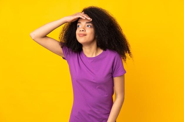 Młoda kobieta afroamerykanka robi gest niespodzianki, patrząc w bok