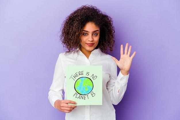 Młoda kobieta afroamerykanów gospodarstwa a nie ma planety b na białym tle uśmiechnięty wesoły pokazując numer pięć palcami.