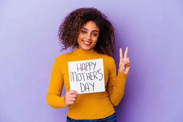 Młoda kobieta afroamerykanów gospodarstwa afisz happy mother's day samodzielnie pokazując numer dwa palcami.