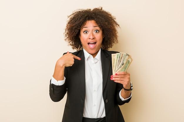Młoda kobieta afroamerykanów gospodarstwa dolarów zaskoczony, wskazując na siebie, uśmiecha się szeroko.