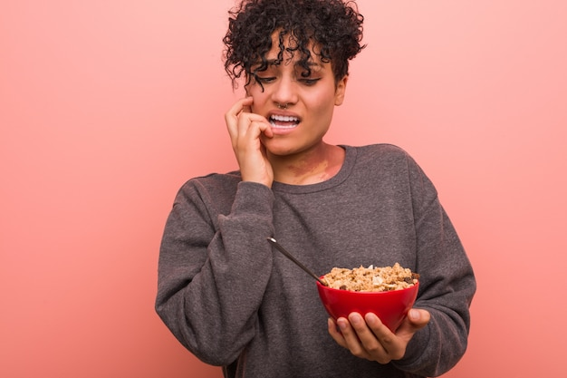 Młoda kobieta afroamerykanów gospodarstwa miska zbóż obgryzanie paznokci, nerwowy i bardzo niespokojny.