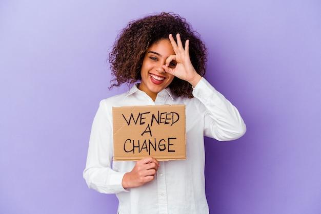 Młoda kobieta afroamerykanów gospodarstwa potrzebujemy plakietki zmiany na białym tle na fioletowej ścianie podekscytowani utrzymując ok gest na oko