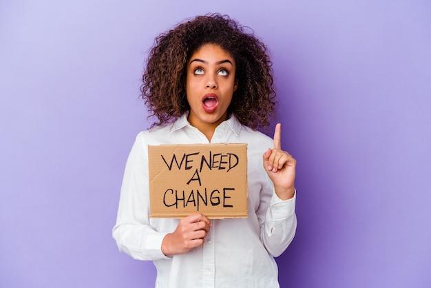 Młoda kobieta afroamerykanów gospodarstwa potrzebujemy plakietki zmiany na fioletowej ścianie skierowanej do góry z otwartymi ustami.