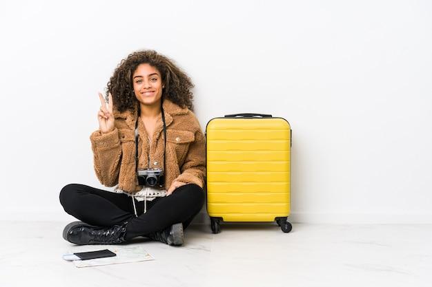 Młoda kobieta afroamerykanów gotowa do podróży pokazuje numer dwa palcami