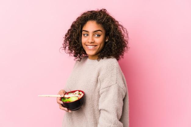 Młoda kobieta afroamerykanów jedzenia makaronu wygląda na bok uśmiechnięty, wesoły i przyjemny.