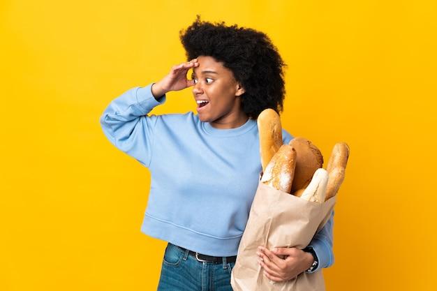 Młoda kobieta afroamerykanów kupuje chleb coś na białym tle na żółtym tle z wyrazem zaskoczenia patrząc z boku