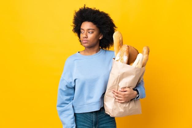 Młoda kobieta afroamerykanów kupuje chleb coś na żółtym tle, mając wątpliwości, patrząc z boku