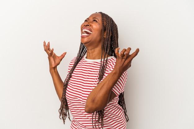 Młoda kobieta afroamerykanów na białym tle krzyczy do nieba, patrząc w górę, sfrustrowana.