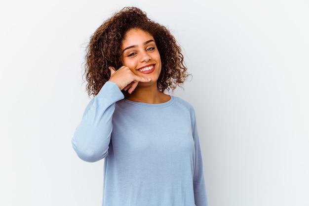 Młoda kobieta afroamerykanów na białym tle na białym tle pokazujący gest rozmowy telefonicznej palcami.