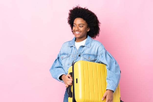 Młoda kobieta afroamerykanów na białym tle na różowym tle w wakacje z walizką podróży