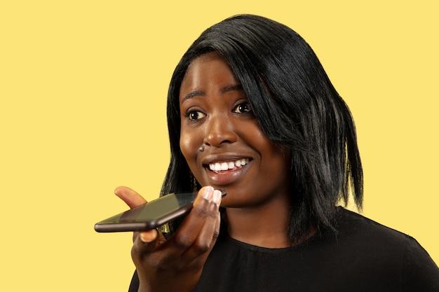 Młoda kobieta afroamerykanów na białym tle na żółty, wyraz twarzy