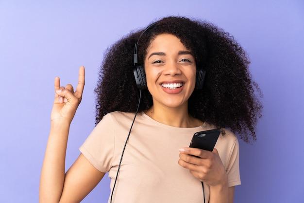 Młoda kobieta afroamerykanów na fioletowym tle słuchania muzyki z telefonu komórkowego czyniąc gest rocka