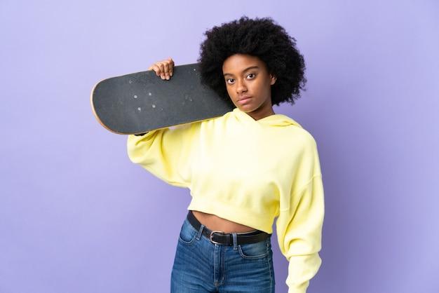 Młoda kobieta afroamerykanów na fioletowym tle ze skate