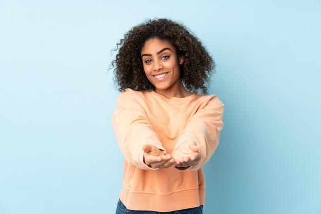 Młoda kobieta afroamerykanów na niebieską ścianą gospodarstwa puste miejsce wyobraźni na dłoni, aby wstawić reklamę