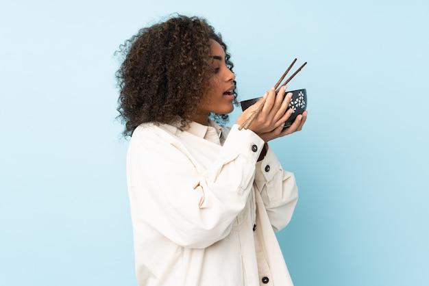 Młoda kobieta afroamerykanów na niebieską ścianą trzyma miskę makaronu z pałeczkami i je