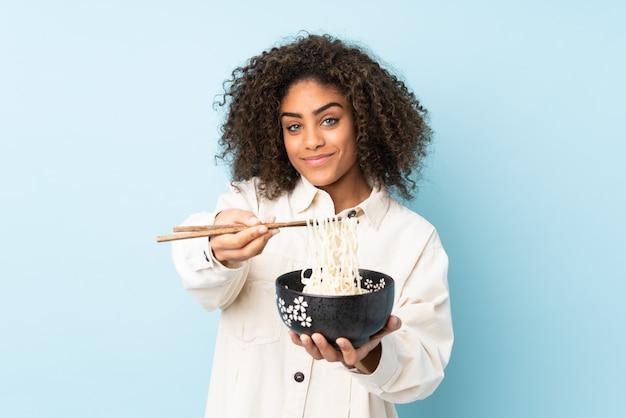 Młoda kobieta afroamerykanów na niebieską ścianą, trzymając miskę makaronu pałeczkami i oferując go