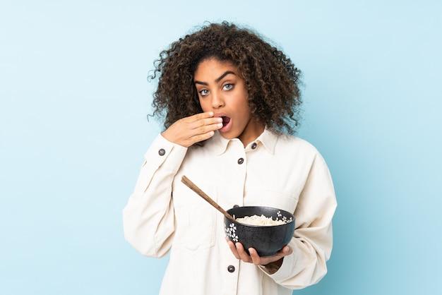 Młoda kobieta afroamerykanów na niebieską ścianą, trzymając miskę makaronu z pałeczkami i zaskoczony
