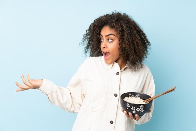 Młoda kobieta afroamerykanów na niebieską ścianą z zaskoczenia wyraz twarzy, trzymając miskę makaronu pałeczkami