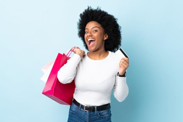 Młoda kobieta afroamerykanów na niebiesko ściany gospodarstwa torby na zakupy i karty kredytowej