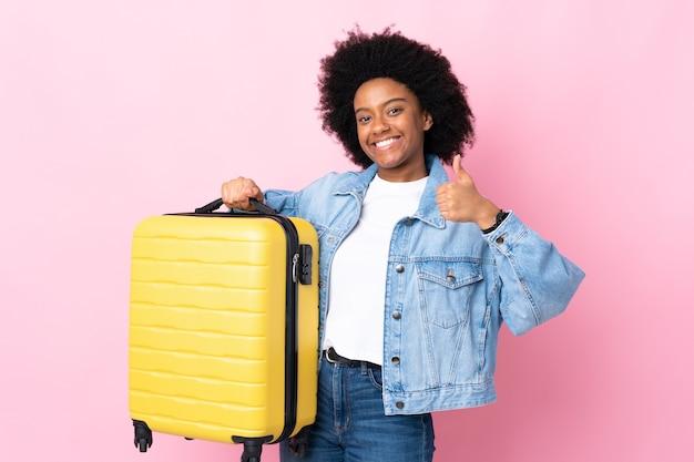 Młoda kobieta afroamerykanów na różowo w wakacje z walizką podróżną iz kciukiem do góry