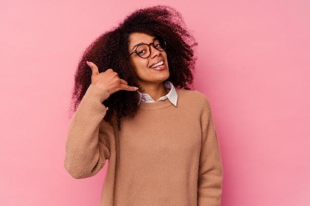 Młoda kobieta afroamerykanów na różowym tle pokazano gest rozmowy telefonicznej palcami.