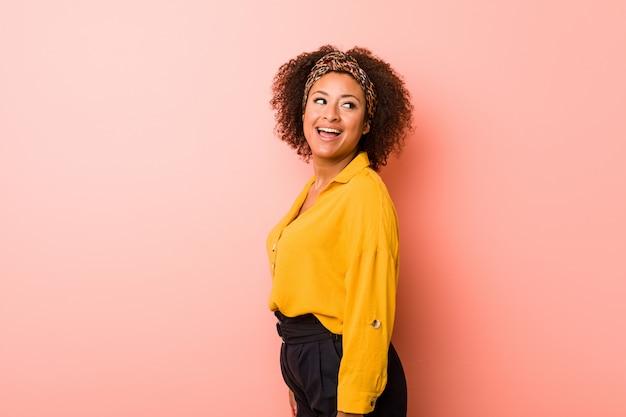 Młoda kobieta afroamerykanów na różowym tle wygląda na uśmiechnięty, wesoły i przyjemny.