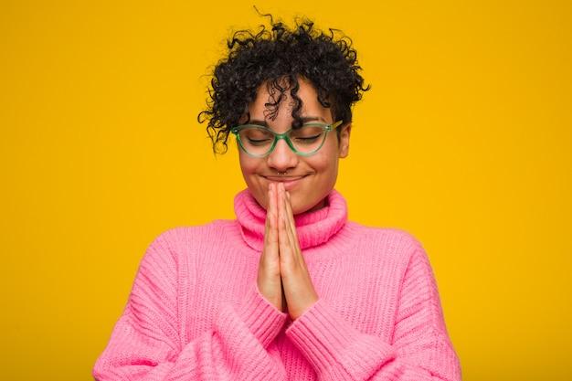 Młoda kobieta afroamerykanów na sobie różowy sweter, trzymając się za ręce w modlić się w pobliżu usta, czuje się pewnie.