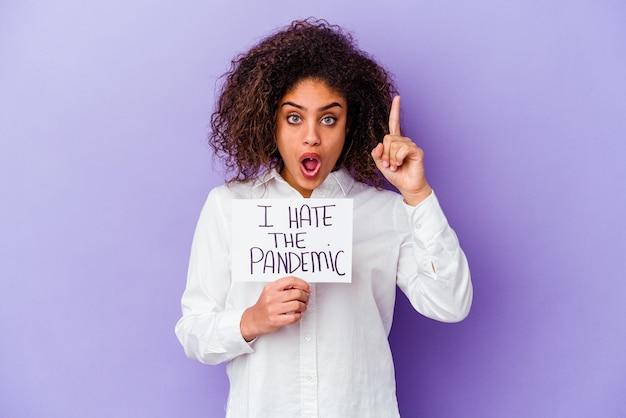 Młoda kobieta afroamerykanów nienawidzę plakatu pandemii na fioletowej ścianie mając pomysł