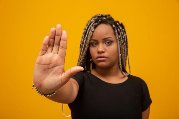 Młoda kobieta afroamerykanów pokazała rękę na znaku, aby przestali z uprzedzeniami rasowymi.