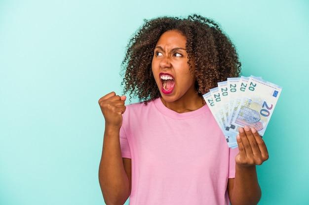Młoda kobieta afroamerykanów posiadających banknoty euro na białym tle na niebieskim tle podnosząc pięść po zwycięstwie, koncepcja zwycięzca.