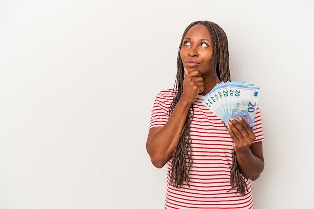 Młoda kobieta afroamerykanów posiadających banknoty na białym tle patrząc w bok z wyrazem wątpliwości i sceptyczny.