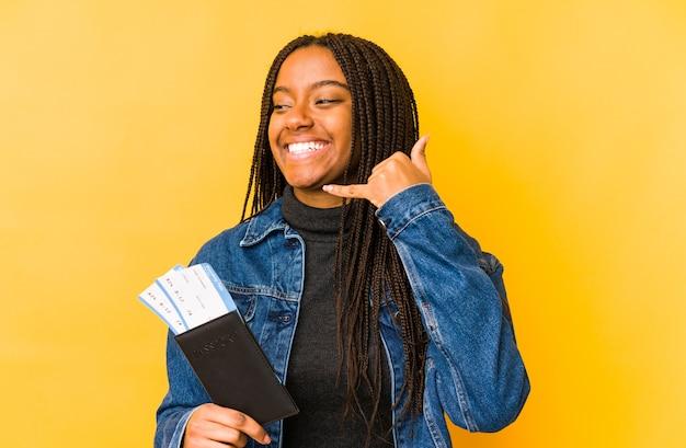 Młoda kobieta afroamerykanów posiadających paszport na białym tle przedstawiający gest rozmowy telefonicznej palcami.