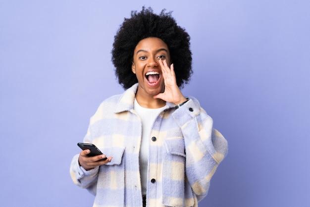 Młoda kobieta afroamerykanów przy użyciu telefonu komórkowego samodzielnie na fioletowo krzycząc z szeroko otwartymi ustami