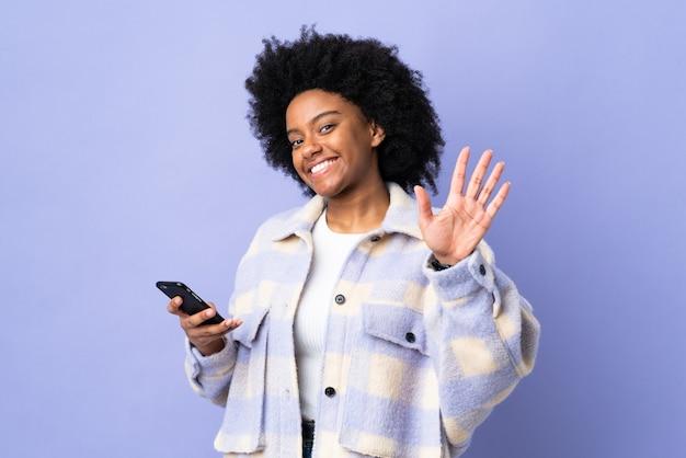 Młoda kobieta afroamerykanów przy użyciu telefonu komórkowego samodzielnie na fioletowo salutowania ręką z happy wypowiedzi