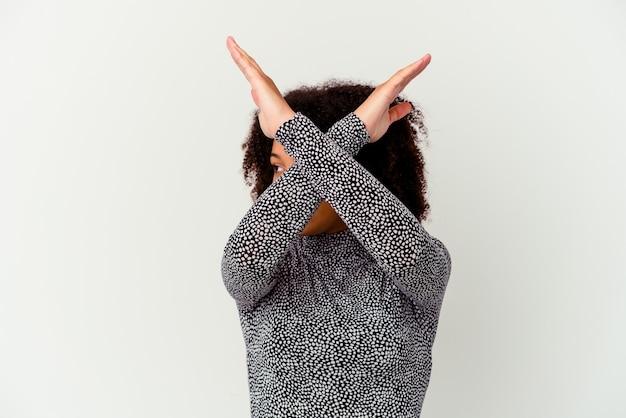 Młoda kobieta afroamerykanów rasy mieszanej na białym tle, trzymając dwie skrzyżowane ręce, koncepcja odmowy.