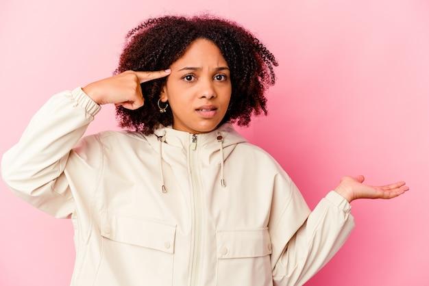 Młoda kobieta afroamerykanów rasy mieszanej na białym tle trzymając i pokazując produkt pod ręką.