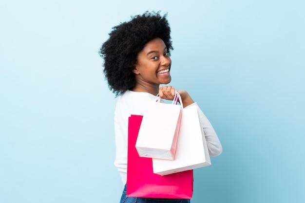 Młoda kobieta afroamerykanów samodzielnie na niebieskim tle gospodarstwa torby na zakupy i uśmiechnięte