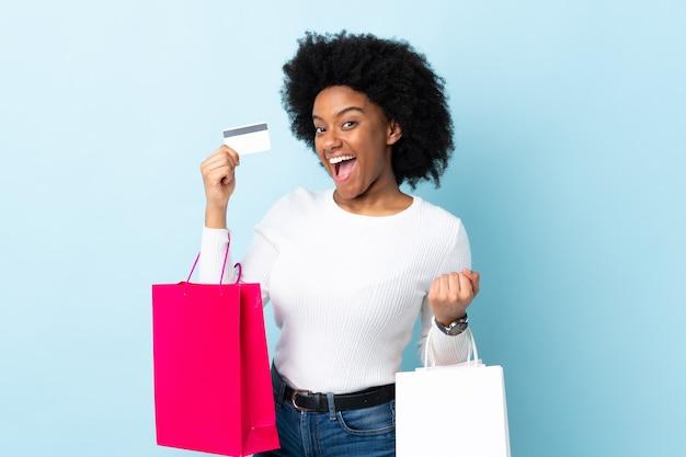 Młoda kobieta afroamerykanów samodzielnie na niebieskim tle, trzymając torby na zakupy i kartę kredytową
