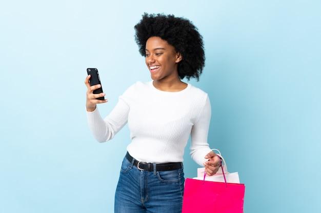 Młoda kobieta afroamerykanów samodzielnie na niebiesko trzymając torby na zakupy i pisanie wiadomości ze swojego telefonu komórkowego do znajomego