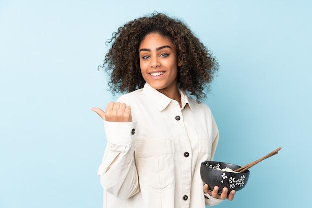 Młoda kobieta afroamerykanów samodzielnie na niebiesko, wskazując na bok, aby przedstawić produkt, trzymając miskę makaronu pałeczkami