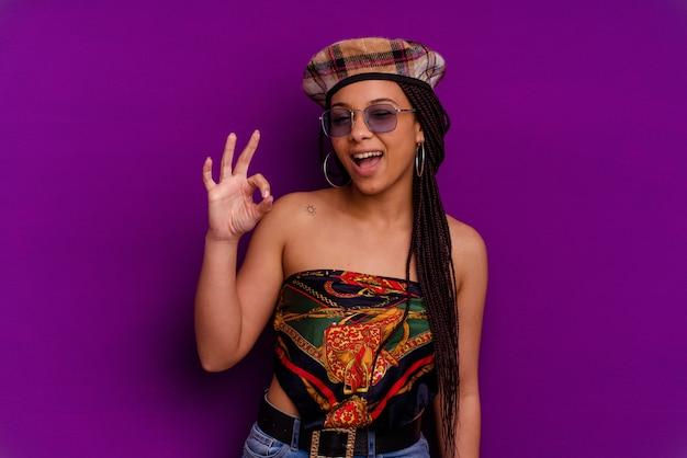 Młoda kobieta afroamerykanów samodzielnie na żółtej ścianie młoda kobieta afroamerykanów samodzielnie na żółtej ścianie mruga okiem i trzyma w porządku gest ręką.