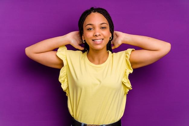Młoda kobieta afroamerykanów samodzielnie na żółtym tle młoda kobieta afroamerykanów samodzielnie na żółtym tle rozciąganie ramion, pozycja zrelaksowana.