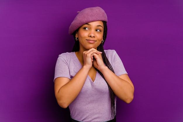 Młoda kobieta afroamerykanów samodzielnie na żółtym tle młoda kobieta afroamerykanów samodzielnie na żółtym tle trzyma ręce pod brodą, patrzy szczęśliwie na bok.