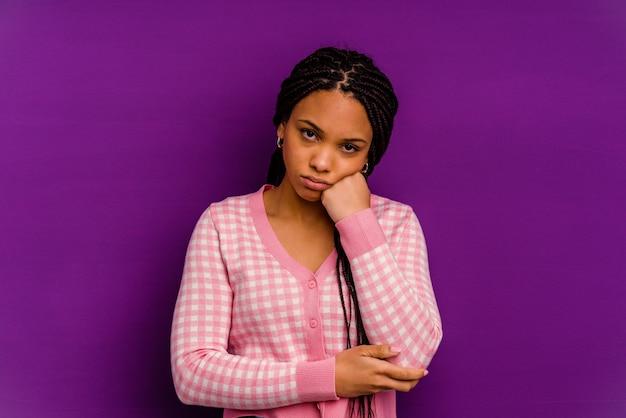 Młoda kobieta afroamerykanów samodzielnie na żółtym tle młoda kobieta afroamerykanów samodzielnie na żółtym tle zmęczona powtarzalnym zadaniem.