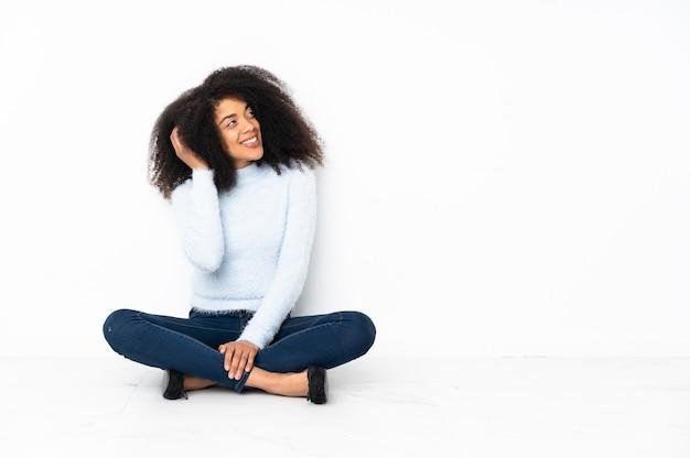 Młoda kobieta afroamerykanów siedzi na podłodze, myśląc pomysł