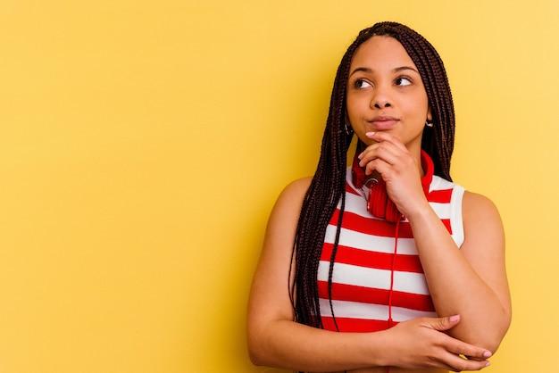 Młoda kobieta afroamerykanów, słuchanie muzyki w słuchawkach na białym tle na żółtym tle, patrząc w bok z wyrazem wątpliwości i sceptycyzmu.